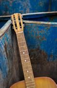 Thrown Away Old Guitar and Dumpster - stock photo