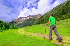 Mountaineer in a green t-shirt with poles, Austria - stock photo