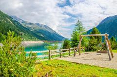 Wooden swing with azure mountain lake, Austria - stock photo