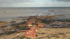 Red bricks washed ashore a sandy beach in Australia Stock Footage