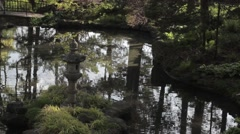 Botanical Zen like garden & pond in the forest, stone bridge and statue - stock footage