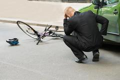 Stock Photo of Sad Male Driver After Collision With Bicycle On Road