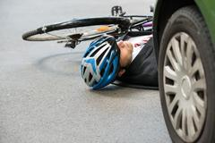 Unconscious Male Cyclist Lying On Street After Road Accident Stock Photos