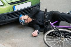 Unconscious Male Cyclist Lying On Road After Road Accident Stock Photos