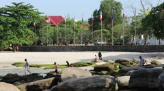 Sokha Beach locals walk on rocks white sand and flags behind Stock Footage
