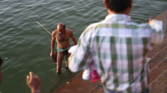 Stock Video Footage of Right to left view of people bathing in Ganges in Varanasi.
