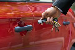 Close-up Of A Person's Hand Holding A Car's Remote Control Pointing To The Do - stock photo