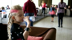 Little cute blonde girl drink water from a bottle in club cafe Stock Footage