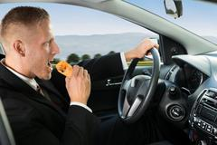 Close-up Of A Young Businessman Eating Snack While Driving Stock Photos