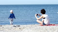 Mother make photo via smartphone of her child daughter play on sea beach Stock Footage