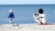 Stock Video Footage of Mother make photo via smartphone of her child daughter play on sea beach