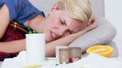 Sick woman blowing nose while she is lying on bed Stock Footage