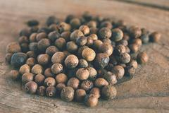 Allspice on an old wooden table Stock Photos