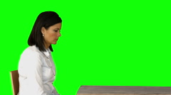 Irritated businesswoman sitting on chair on green screen Stock Footage