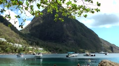 St. Lucia Caribbean Sea 119 small Piton with green foliage and boats Stock Footage