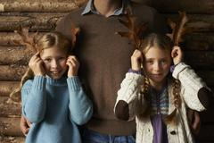 Girls using leaves as antlers with father - stock photo