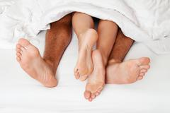 feet of couple in bed - stock photo