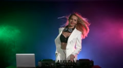 Beautiful, smiling, sexy dj girl in white jacket, headphones playing music and Stock Footage