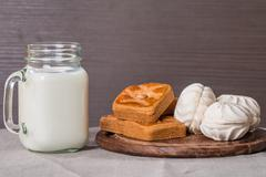 Fresh milk in glass and sweet cookies with zephyr - stock photo