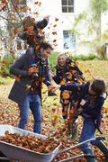 Family playing in autumn leaves - stock photo