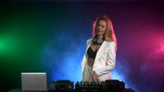 Beautiful, charming, smiling dj girl in white jacket, headphones playing music Stock Footage