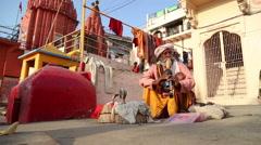 Indian man hypnotising a snake with music at street in Varanasi. - stock footage