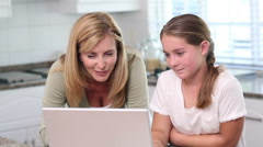 Mother and daughter using laptop - stock footage