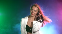 Beautiful, charming, smiling dj girl in white jacket, headphones on her ear Stock Footage