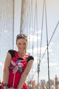 Woman with novelty pinwheel on urban bridge - stock photo
