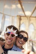 Couple in novelty sunglasses taking picture on urban bridge Stock Photos