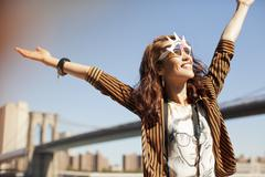 Woman in novelty sunglasses standing by urban bridge Stock Photos