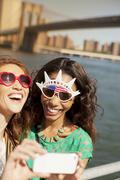 Women in novelty sunglasses taking picture by city cityscape Stock Photos