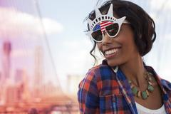 Woman wearing novelty sunglasses on city street Stock Photos