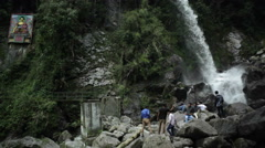 Indian men and boys at buddha waterfall, long shot Stock Footage