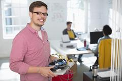 Businessman carrying cords and laptop in office Stock Photos