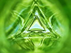 Abstract image of a triangle glass bottle emerald green color background Stock Photos