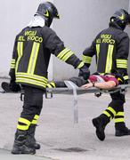 Firefighters carried the injured away on stretchers Stock Photos