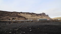 Black rock beach iceland with buildings looking onto mountains Stock Footage