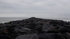 Black rock beach iceland with rocks going out to water Stock Footage