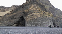 Tourists on black rock beach iceland Stock Footage
