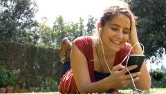 Attractive woman using mobile phone with headphones smartphone 4k Arkistovideo