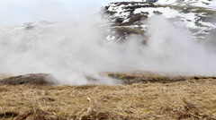 Strokkur Geysirs with geo thermals and snow covered mountains in iceland Stock Footage