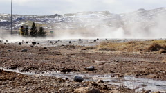Stream in Strokkur Geysirs with geo thermals and snow covered mountains iceland Stock Footage