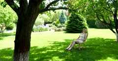 A blonde girl resting in a green park on a wicker cane chair Stock Footage