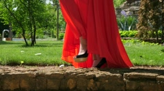 Blonde young girl in red dress posing in a green park location Stock Footage