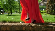 Stock Video Footage of Blonde young girl in red dress posing in a green park location