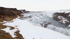 Gullfoss waterfall wide in spring with snow and ice on rocks in iceland Stock Footage