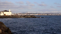 Sea and blue sky with rocks/houses in foreground in reykjavik, iceland Stock Footage