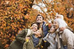 Family playing in autumn leaves in park - stock photo