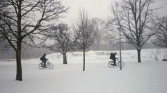 Bicycling in snow covered park - stock footage
